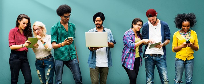 Group of students looking at phones and laptops